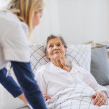 caregiver with her senior patient in bed