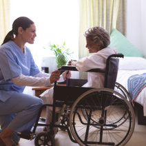 caregiver and her senior patient on a wheelchair