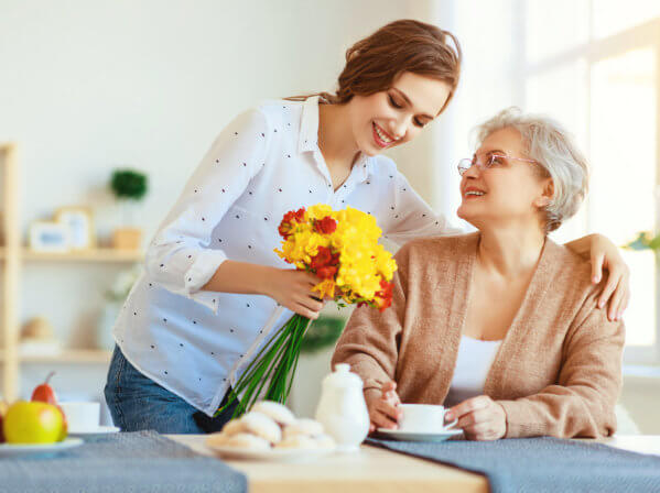 caregiver giving flowers to a senior woman