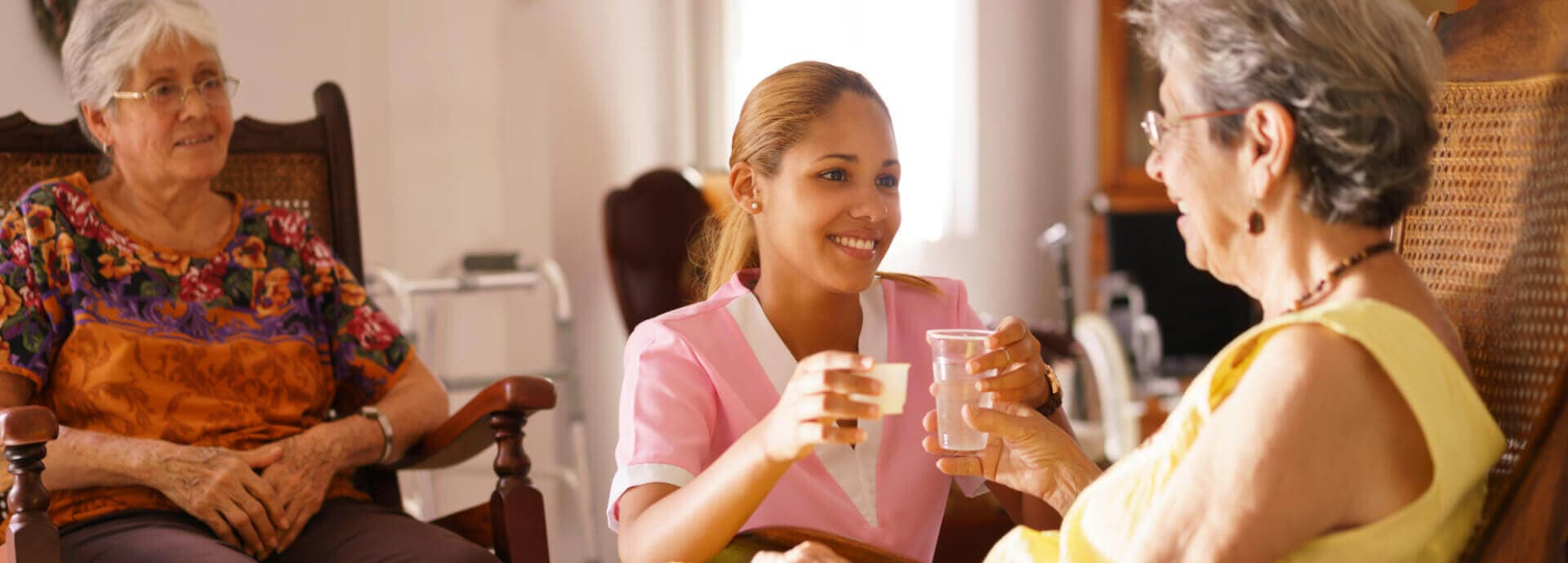 caregiver giving her senior patient some water