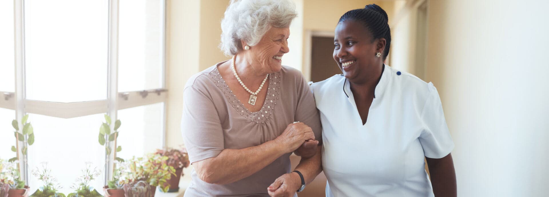 senior woman walking with her caregiver