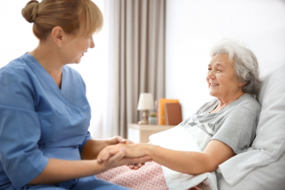 senior woman in bed with her caregiver